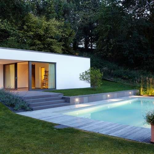 Moderner pool mit beleuchtung exklusiv design mit naturstein grauwacke sitzfläche und außen sauna rheingrün gartengestaltung