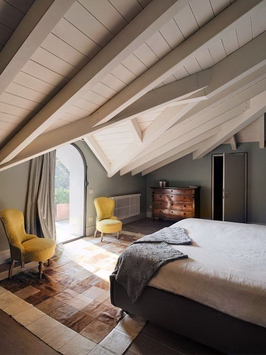 In an under-the-eaves bedroom, chairs covered in soft yellow linen are surrounded by a palette of neutral grays and browns.