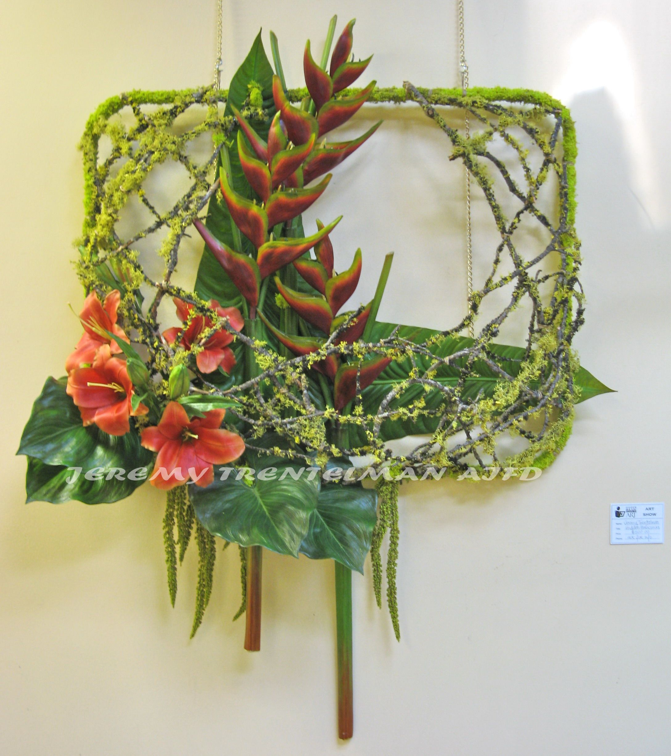 "Hidden Haliconia: 36""x48"". The frame is a repurposed military jeep window that has been covered in mosses. The ""nest"" was created with mossy branches and is 12"" deep creating a pocket for the floral arrangement to sit in. Upright haliconia, lilies, and tropical foliage. This was one of several pieces on exhibit at my last art show."