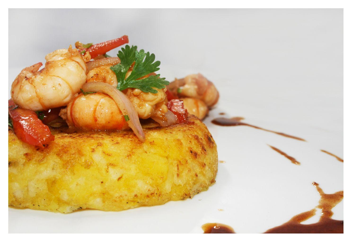 Shrimp stir-fry over Runtus potato tacu tacu. Chef Marilu Madueño