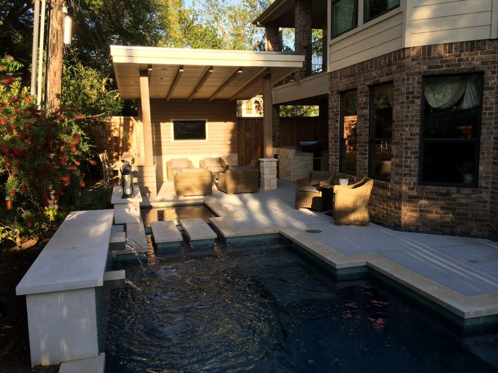 beautiful built in pool with fountains next to outdoor living