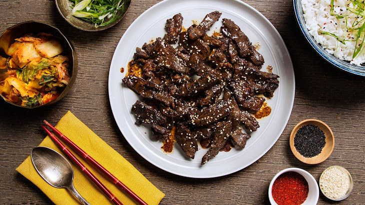 Bulgogi (Korean BBQ Beef) Recipe Main Dishes with water, soy sauce, white sugar, sesame oil, garlic powder, onion powder, rib eye steaks, vegetable oil, scallions, black sesame seeds, steamed white rice