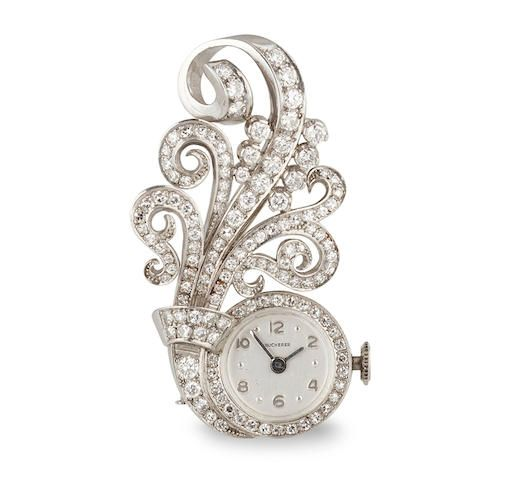 A diamond watch brooch of scroll design, set throughout with single-cut diamonds; dial signed Bucherer; estimated total diamond weight: 1.10 carats; mounted in platinum; length: 1 3/4in. Z