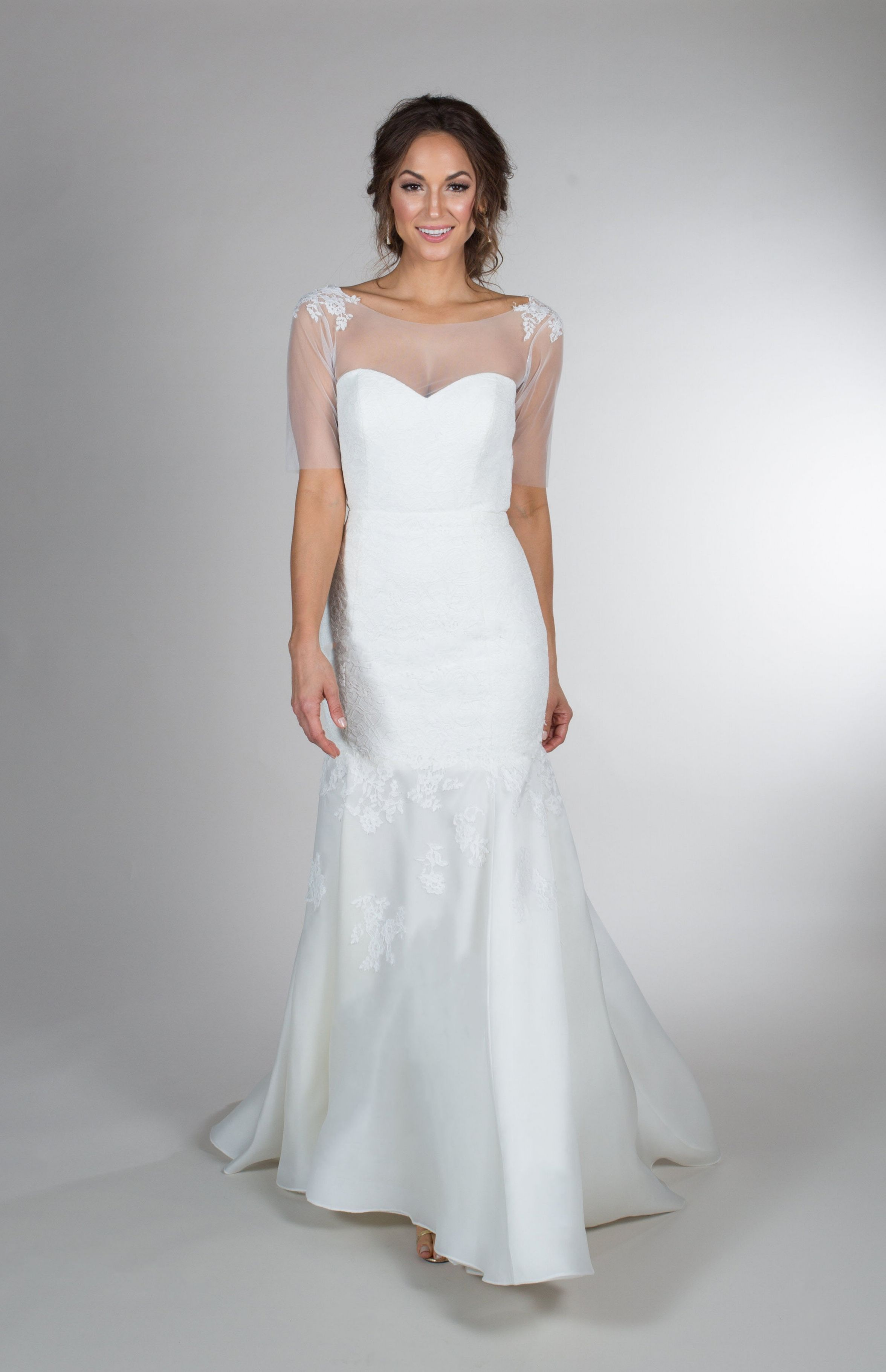 This trumpet style wedding gown features an illusion bodice with