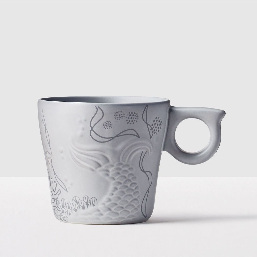 Anniversary Siren Tail Mug. An undersea scene with a hint of the Siren's tail swimming off in hues of gray.