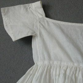 Girl's Underdress  c 1790    of white cotton with large squarish neck, high waist, short straight sleeves, full skirt, back opening with waist ties, 28 in or 70 cm long