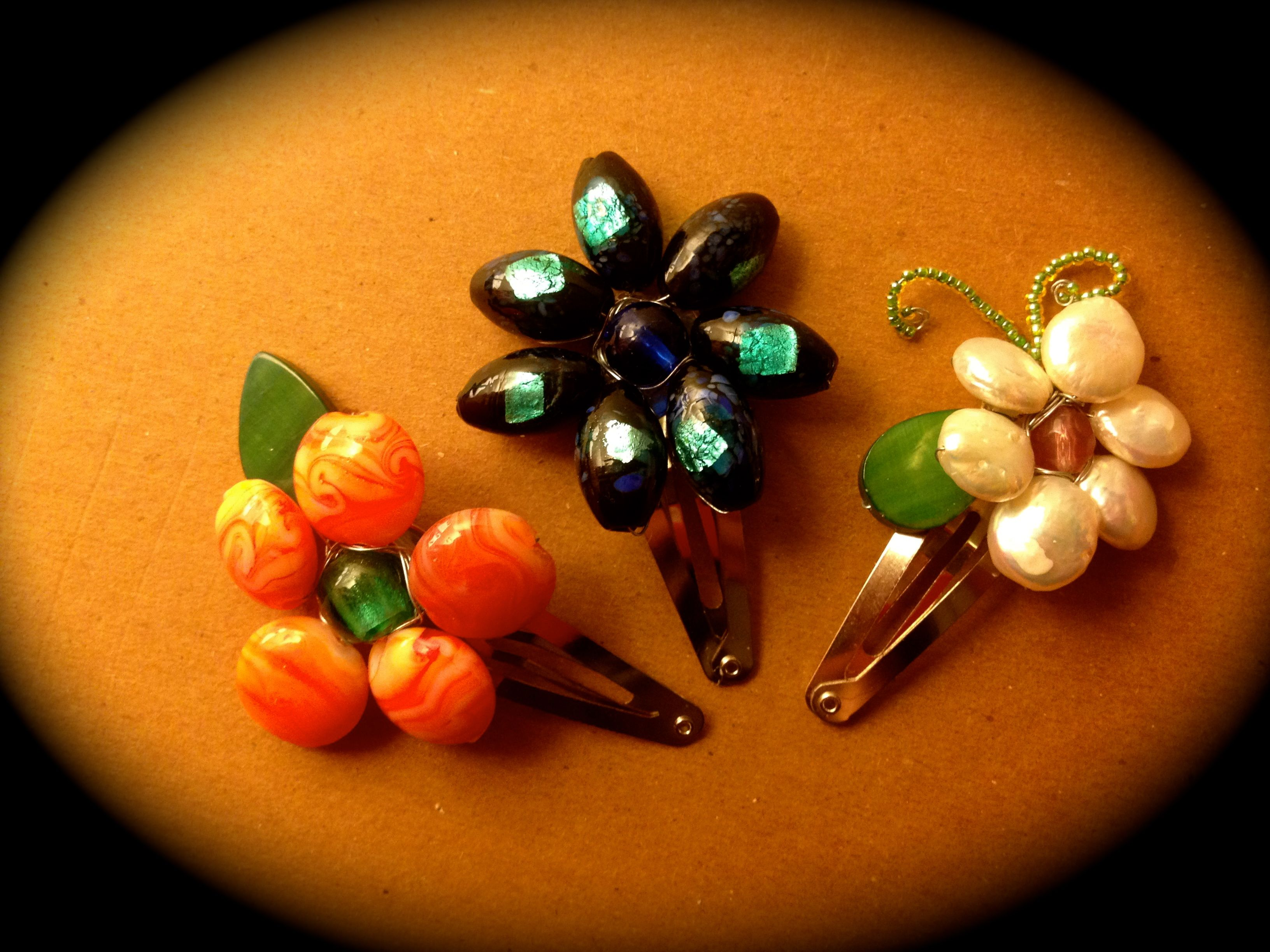 Beaded Hair Clips    All you need are:  1. Large size bead (Petals)  2. Small size beads (center)  3. Fine wire (color of your choice, 26 guage wire)   4. Snap hair clips  5. Hot glue gun/glue sticks   6. Scissors   7. Flat head pliers (optional, great for pulling the wire through the center bead)     How to make them:    Start with one 18-24 inch 26 gauge wire, depending on the size of the beads.    Thread the single wire through the center bead hole (the hole must be large enough to enable…