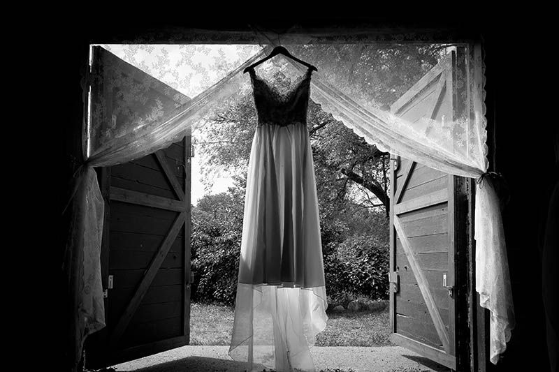 black and white vintage wedding dress detail shot in open barn ...