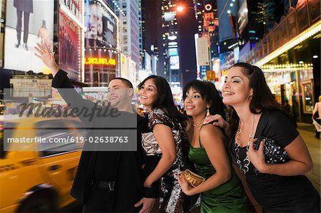 Hispanic friends hailing taxi cab  – Imagem © Masterfile.com: Fotografias, vetores e ilustrações criativas de arquivo para sites, telefones celulares e impressão.