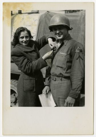 A Czech Girl Pins Something Onto The Uniform Of An American