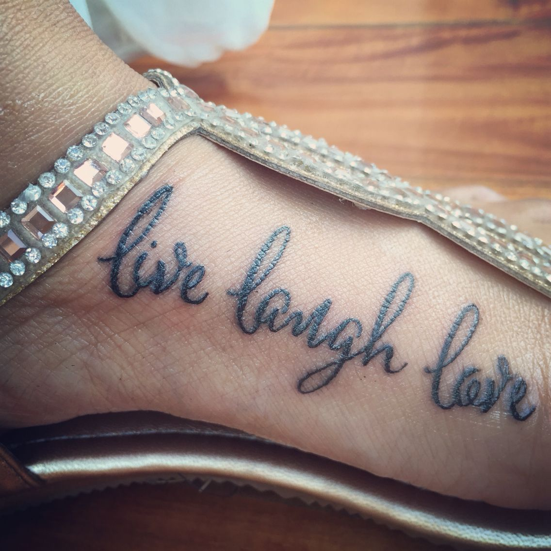 Live laugh love tattoo on the inside left foot Love