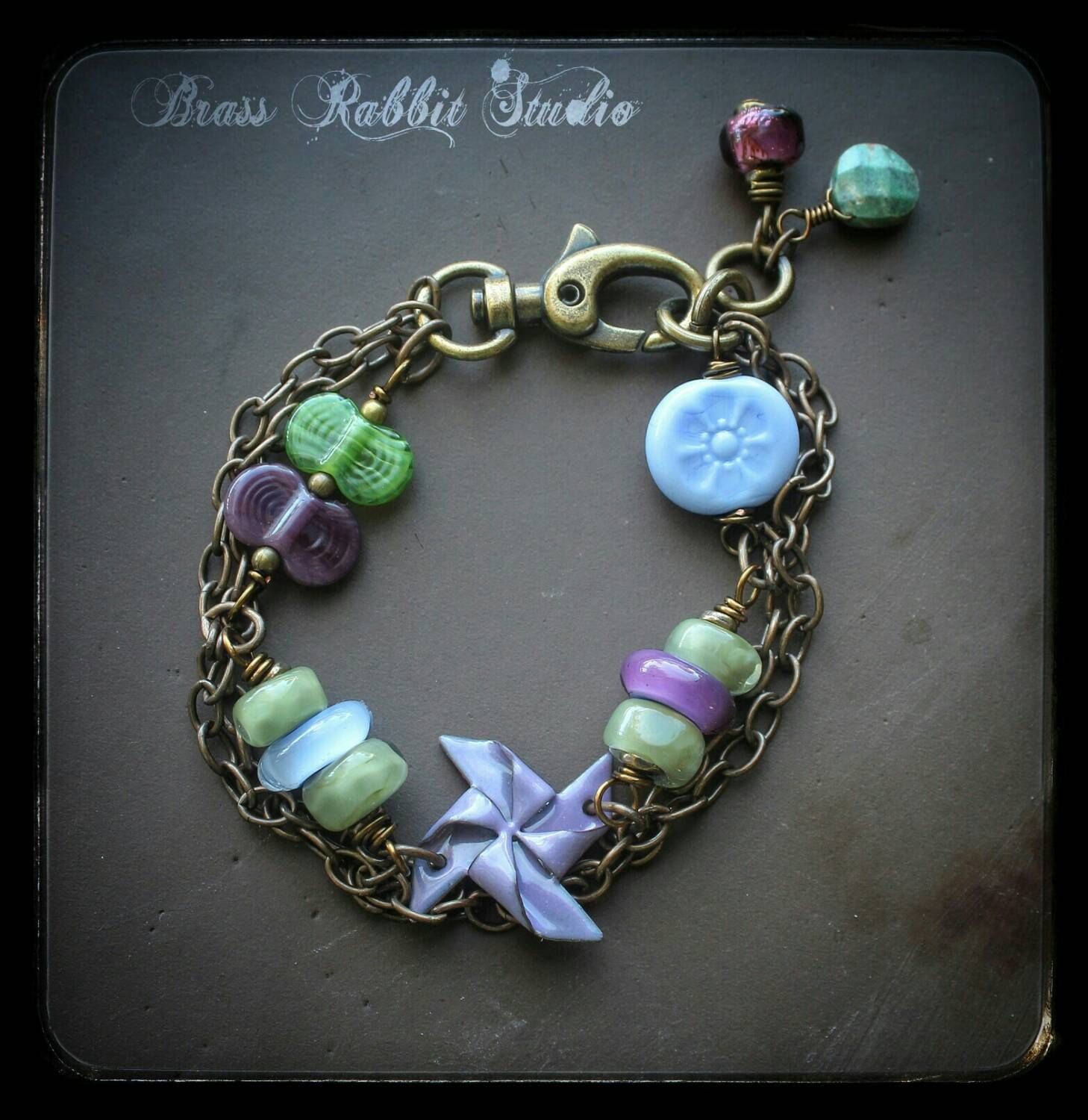 Mixed media bracelet with Lampwork and enameled pinwheel by brass