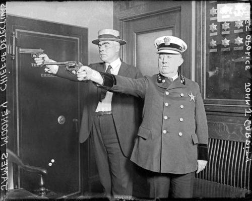 Chief of Detectives Captain James Mooney and Chief of Police Colonel John J. Garrity aim handguns for reporters inside a police station. DN-0072175. #chicago #history #chicagopolice #crime