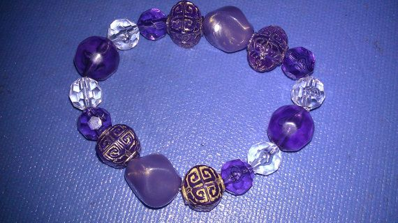This bracelet features acrylic purple and clear beads in different sizes and textures.