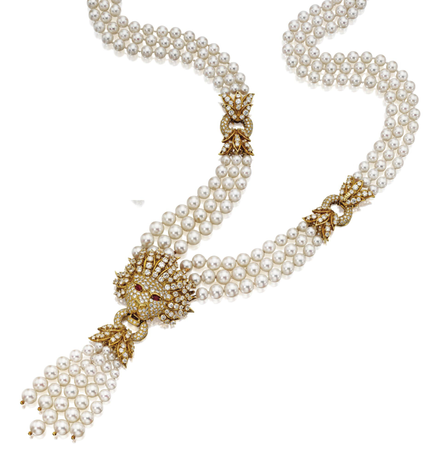 CULTURED PEARL AND DIAMOND LION'S-HEAD NECKLACE/BRACELET COMBINATION, VAN CLEEF & ARPELS, NEW YORK, 1981.  The triple-strand necklace composed of numerous cultured pearls, decorated centrally with a lion's-head ornament supporting a cultured pearl tassel, the whole set with numerous round diamonds, the lion also accented with pear-shaped ruby eyes, mounted in 18 and 14 karat gold, length 24 inches, detaches to form a shorter necklace and bracelet, signed VCA