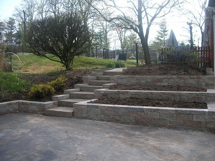 Tiered Side Driveway Retaining Wall Tiered Retaining Wall Lake House Backyard Landscaping Landscaping On A Hill Backyard
