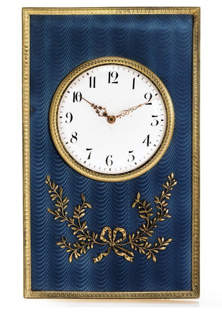 A Fabergé gilded silver and translucent enamel desk clock, workmaster Henrik Wigström, St. Petersburg, 1903-08. Of rectangular shape, enameled translucent steel blue over a guilloché ground and applied with a ribbon-tied silver spray of foliage, the borders chased with acanthus leaves, white enamel dial.