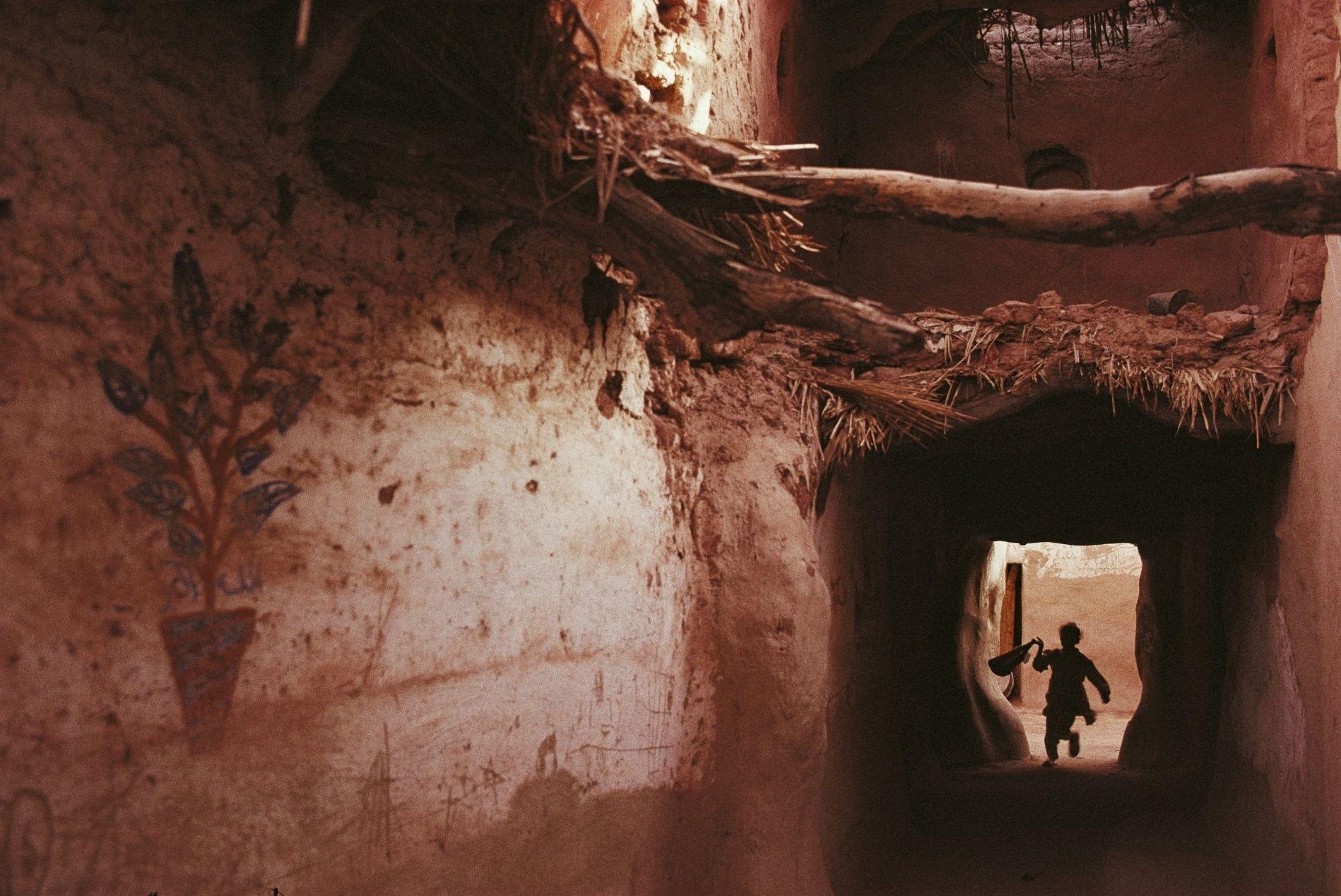 Criança corre entre as paredes de barro de Balat, um vilarejo no oásis de Dakha, um dos sete oásis do Deserto Oriental, no Egito. O local foi uma cidade importante no Antigo Império egípicio
