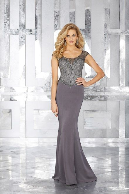 MGNY 71603. Look ravishing at your next formal event by wearing MGNY Style 71603! This lovely crepe gown features a lace top with a beaded neckline and waistline trim. MGNY Style 71603 is available in Charcoal and Eggplant.