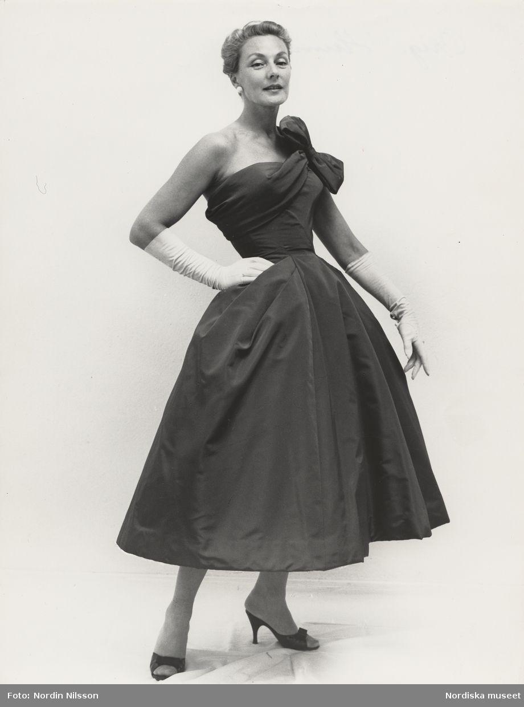 Original J. Heim, 1956. Modell i klänning med rosett på ena axeln, handskar och aftonskor. Foto: Nordin Nilsson