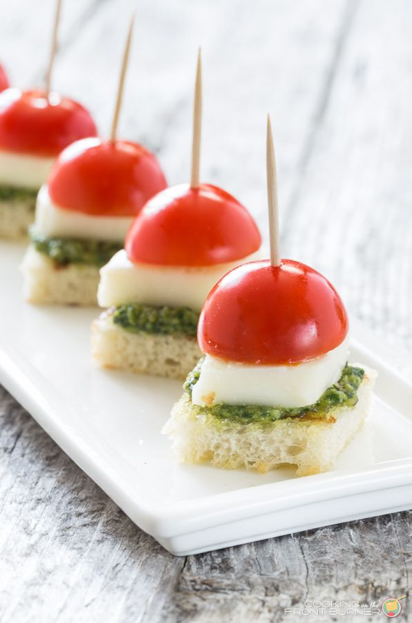 If you are looking for a healthier appetizer, serve these easy Caprese Bites with Pesto at your next gathering.  You will love the juicy tomatoes, tangy mozzarella with fresh basil pesto on a crostini type bread! #caprese