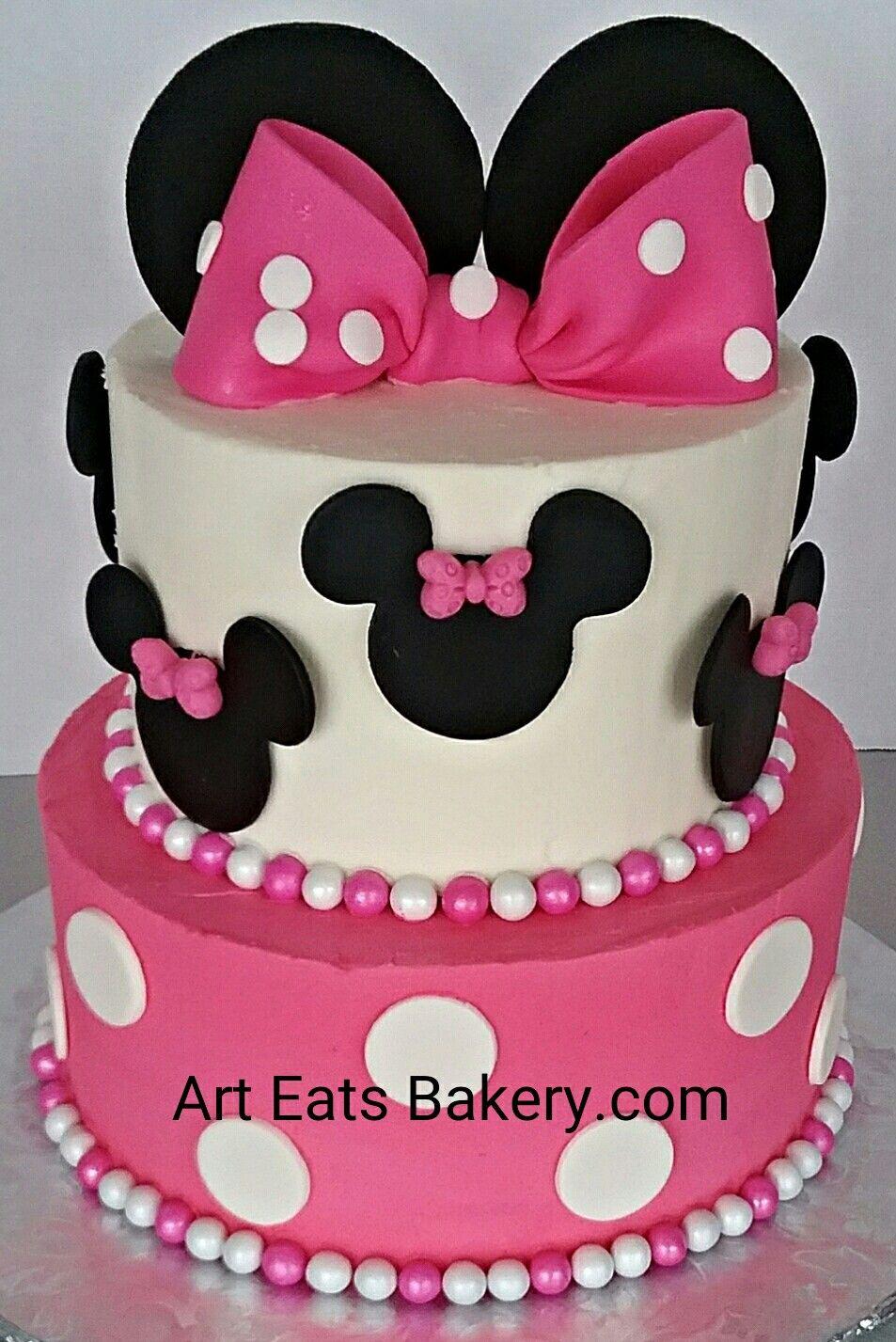 Two tier pink and white buttercream Minnie Mouse birthday cake with fondant ears and polka dot Bows       http://www.arteatsbakery.com