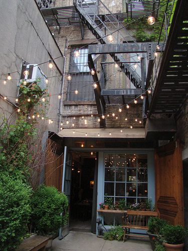 "We love strands of white string lights for outdoor spaces. Our favorite layout? A canopy of them overhead in a zigzag pattern. It looks so casual and somehow "" European. Now to keep the squirrels from chewing the wires apart"