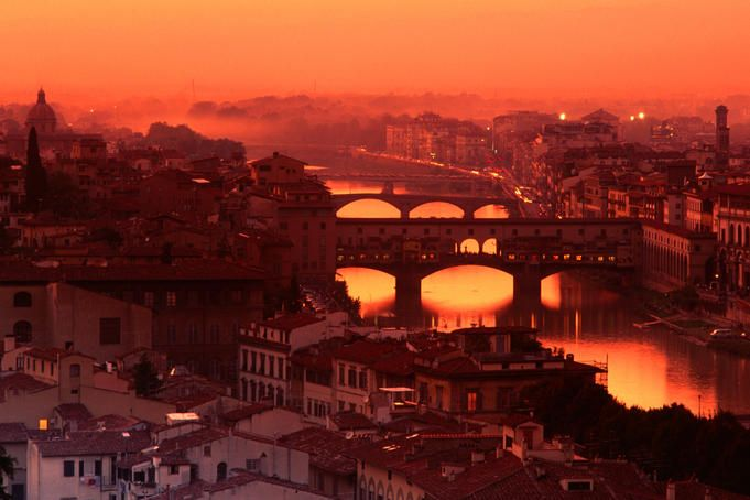 High angle view of Arno River and Ponte Vecchio at sunset, Florence, Italy.