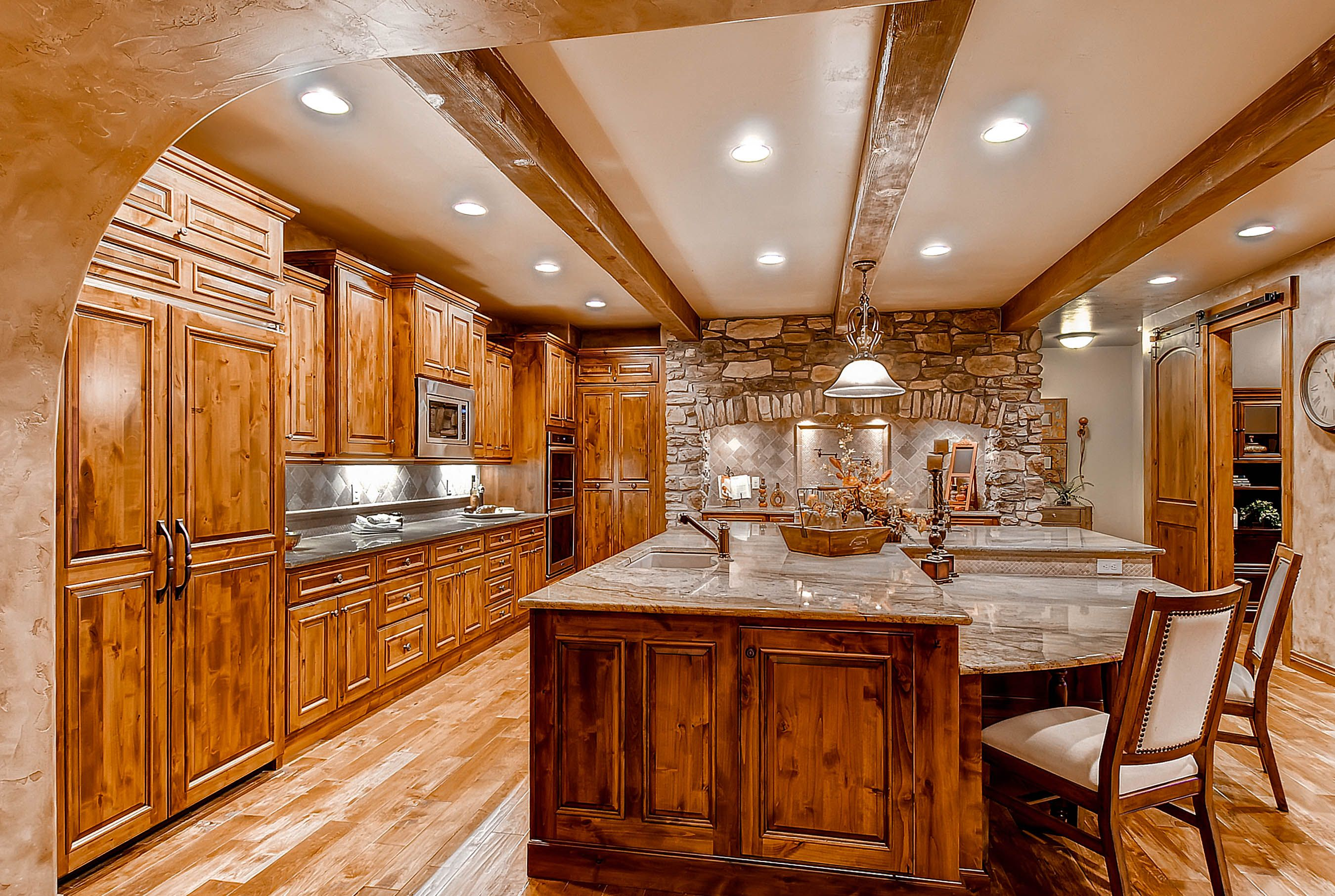 Custom island with hard wood cabinetry, wood beams create the length in the kitchen design. Built in appliances.