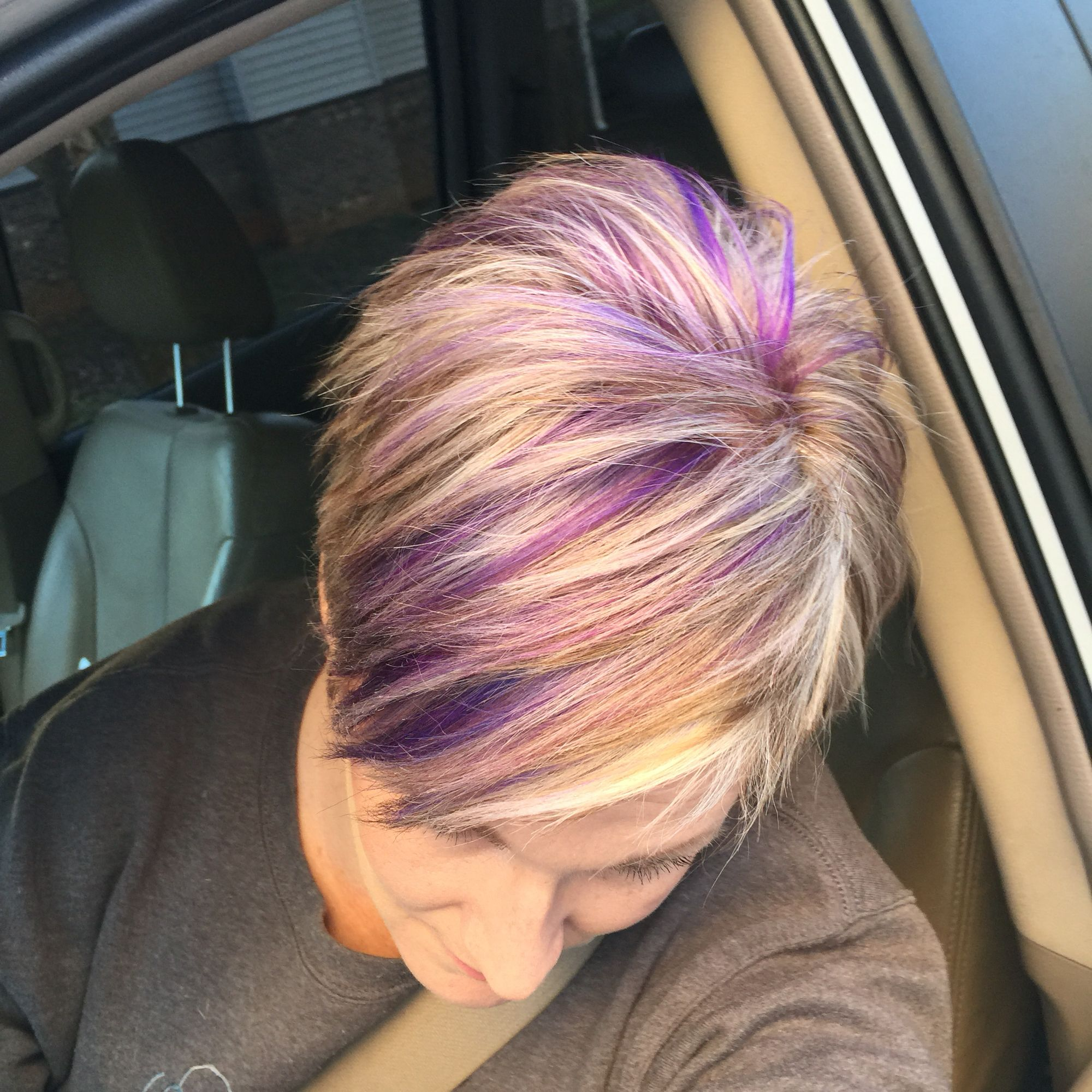 Blonde pixie haircut with purple and fuchsia highlights
