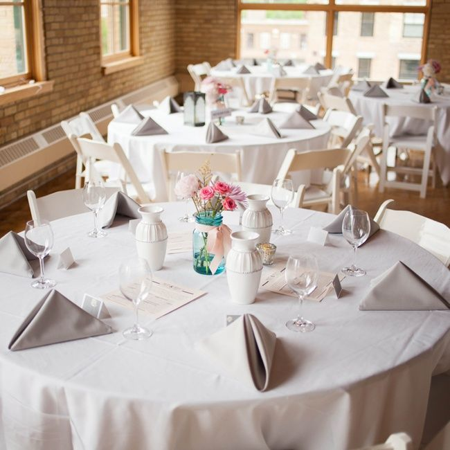 Molly and Matt chose simple rustic decor for their reception. Blue mason jars tied with pink ribbons and linens in a neutral color palette topped the tables.
