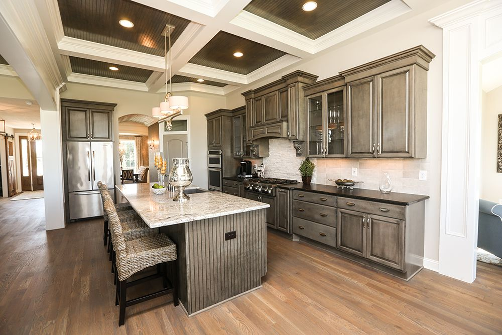 Kitchen in JV Model Home #kitchen #jerome #village #model #home #coffered #ceiling #cabinets #bead #board #pantry #dining #room #sherwin #williams #backsplash #3 #pillar #homes #plain #city #ohio #dublin #schools #custom #luxury #dream #real #estate #builder #trim #painted #doors #lighting #ideas #idea #hardwood #flooring #oversized #island #interior #design #open #floor #plan #foyer #arch #way #heavy #sun #room