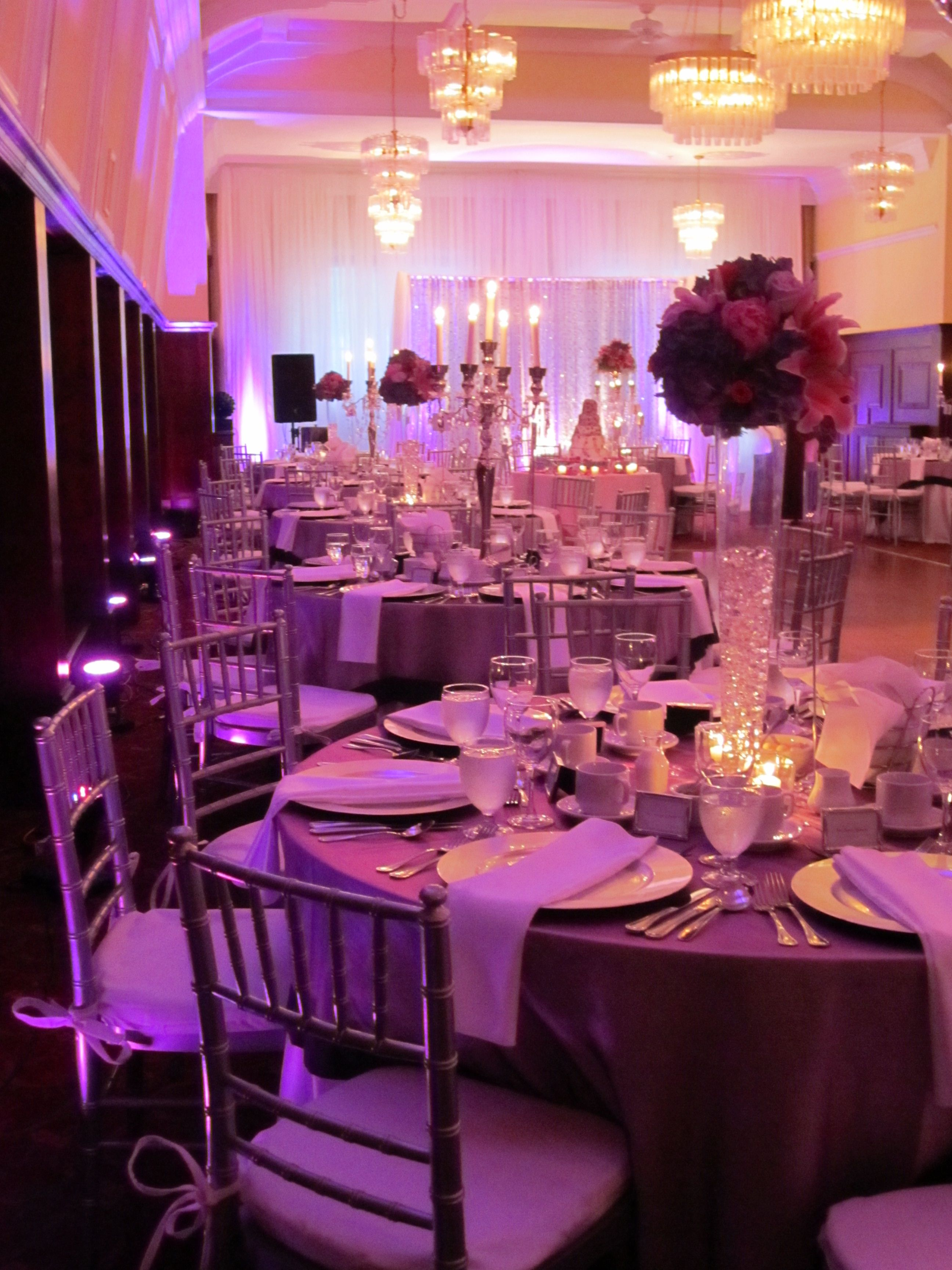 Wow. Silver wedding decor with purple uplighting and white drapes ...