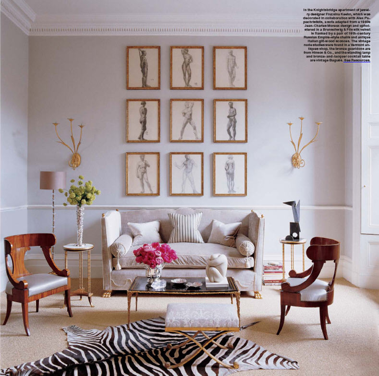 Gallery wall with gold frames and black/white prints, neutral paint and furniture, zebra rug, a few pops of color.