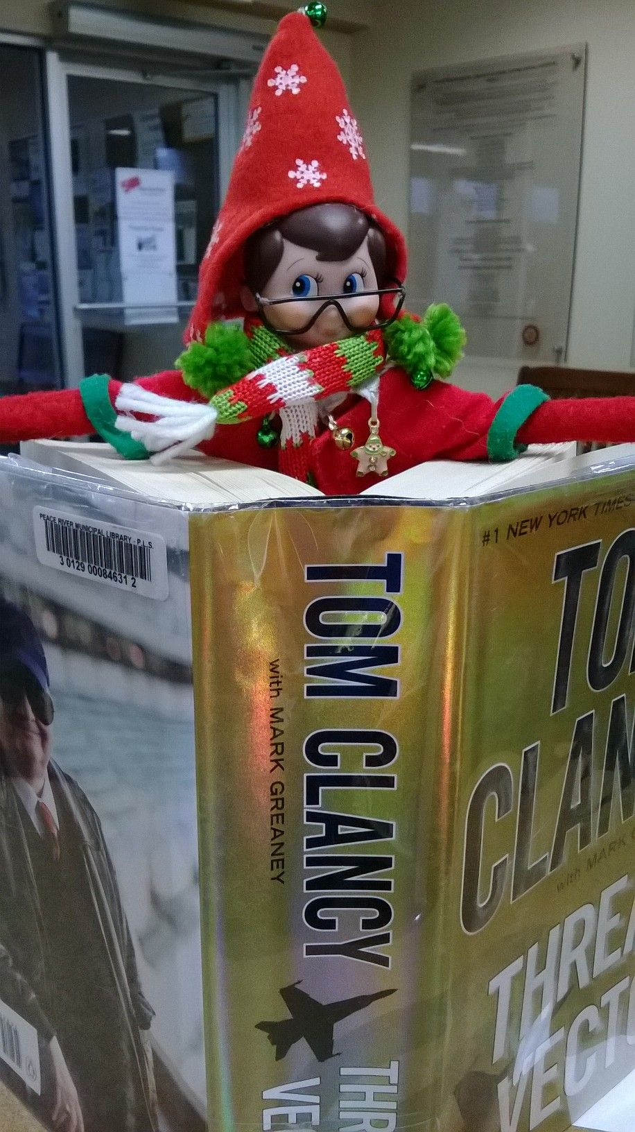 Our elf is doing some reading in our tom clancy book