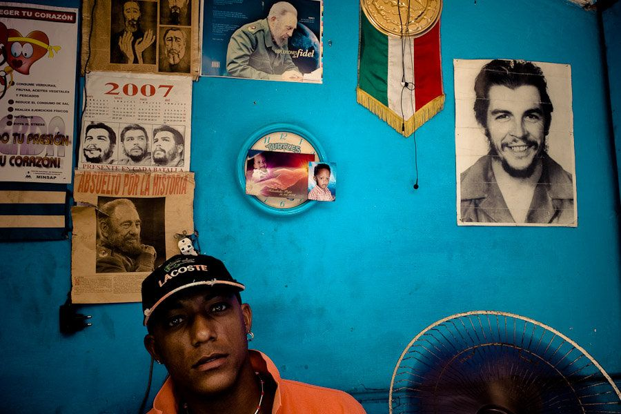 A Cuban watchmaker works in front of a wall covered by pictures of the Cuban Revolutionary leaders in Havana, Cuba.