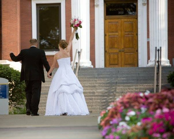 Groom David Gleason ('03) and bride Andrea ('04) celebrating their marriage in front of Buchtel Hall