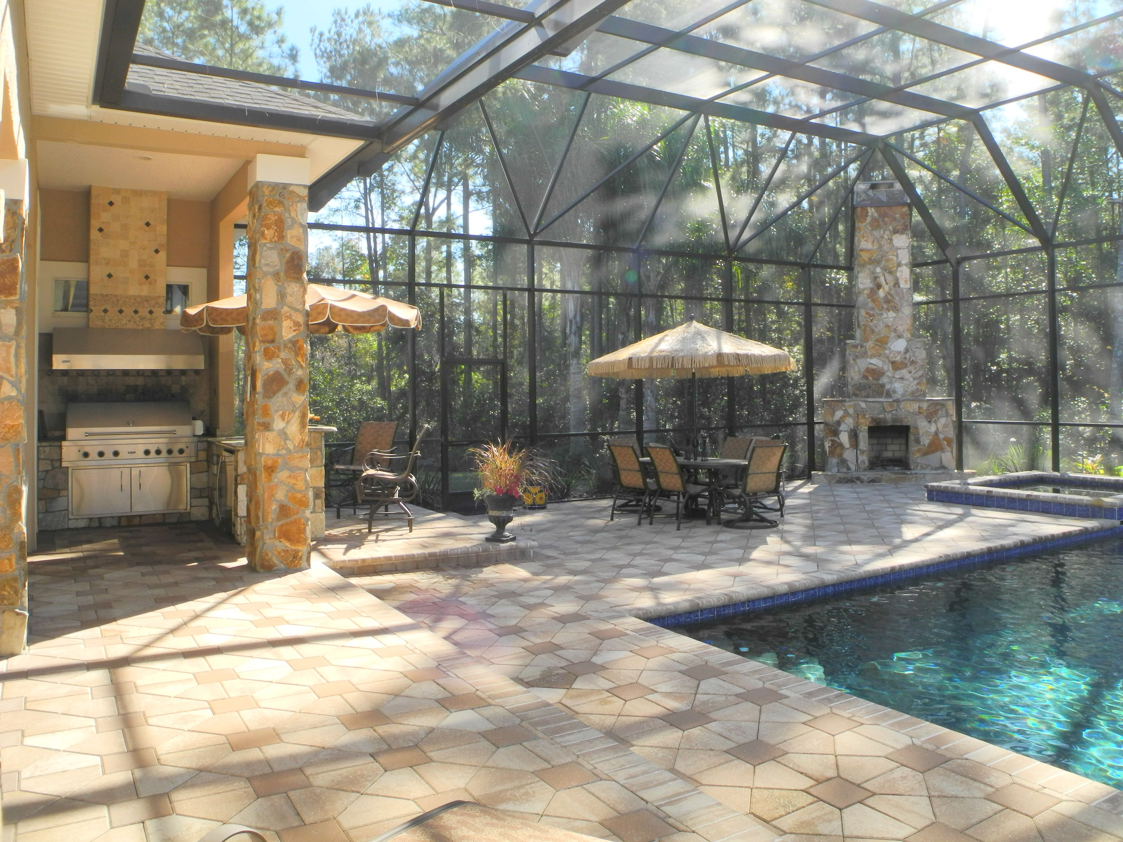 Stone outdoor kitchen with matching stone columns and wood burning
