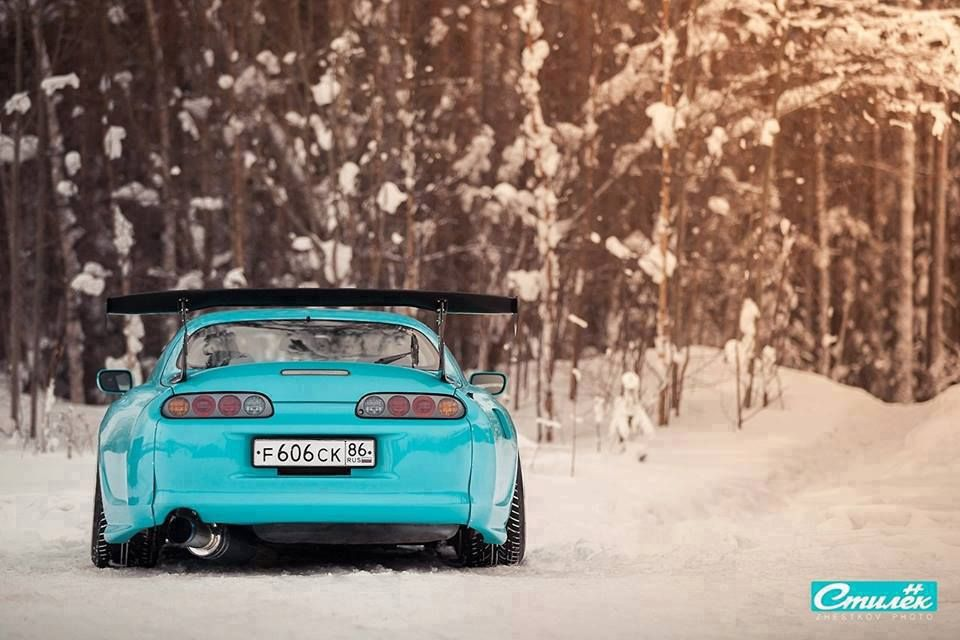 Turquoise Toyota Supra In The Snow. Rear Shot Looking Low
