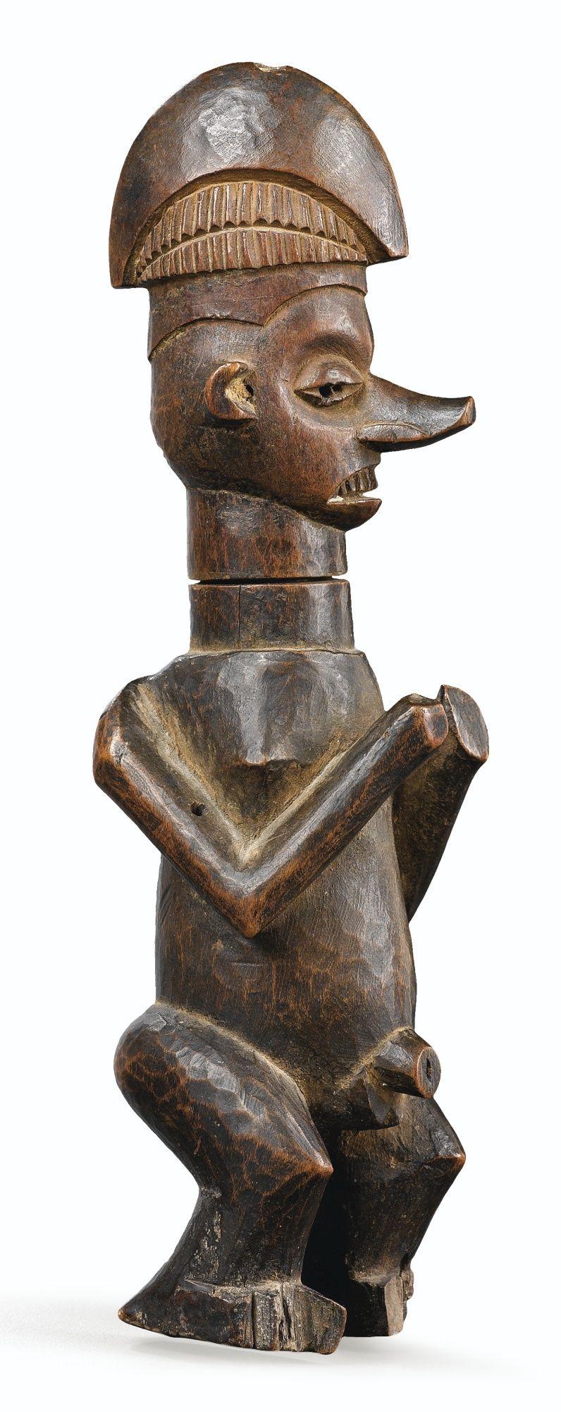 Statue / receptacle Yaka Collected 1910-20 - les sculptures-réceptacles kumdu di mpemba, aux bras percés de trous de suspension, servaient à contenir des ingrédients employés dans les cérémonies d'investiture. Ici, le sommet de la coiffe de dignitaire contient une petite charge, autre indice du rôle rituel dont elle était investie.
