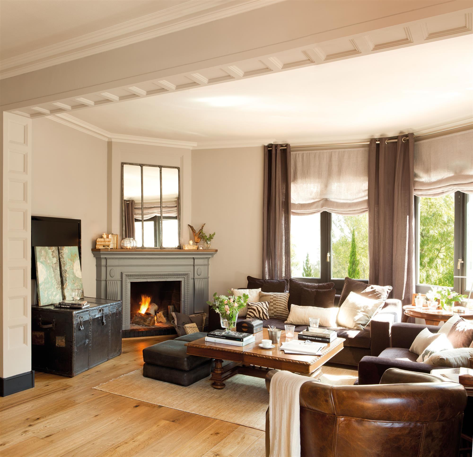 Salón presidido por una chimenea, con sofás de piel marrón y ...