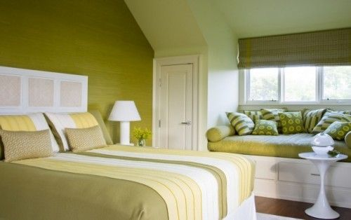 A strong wall color paired with a crisp, white ceiling and trim accentuates the angle of the roofline in this springlike bedroom. A built-in window seat is a great way to take advantage of a nook beneath the window in a converted attic space.