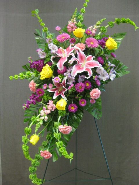 Standing Spray With An Array Of Mixed Bright Flowers Such As Lilies Roses Asters Funeral Flower Arrangements Casket Flowers Beautiful Flower Arrangements