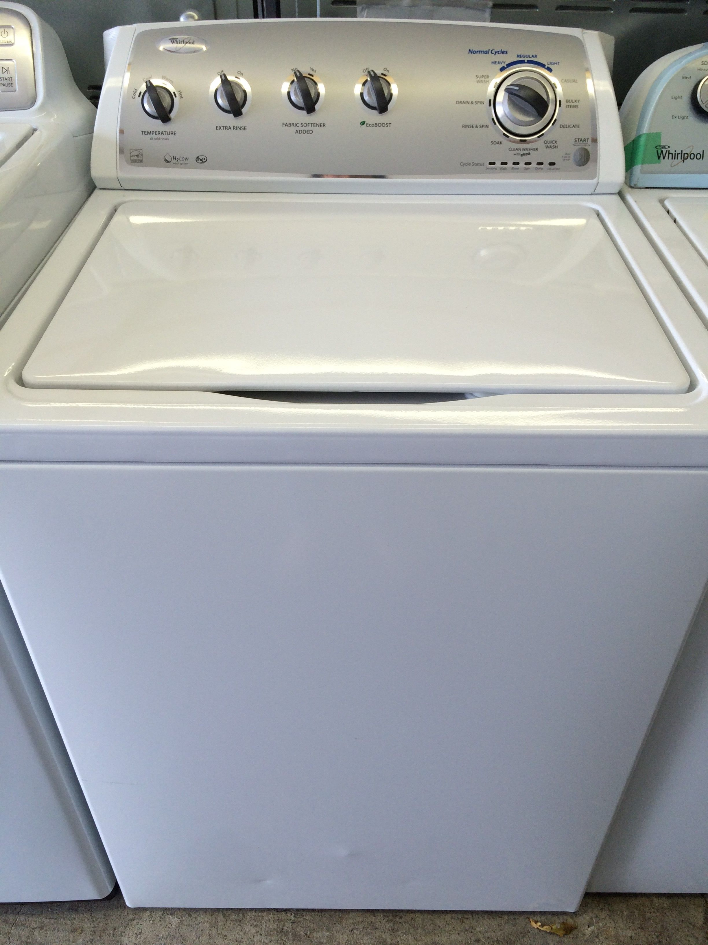 whirlpool top load washer in white appliance store located in