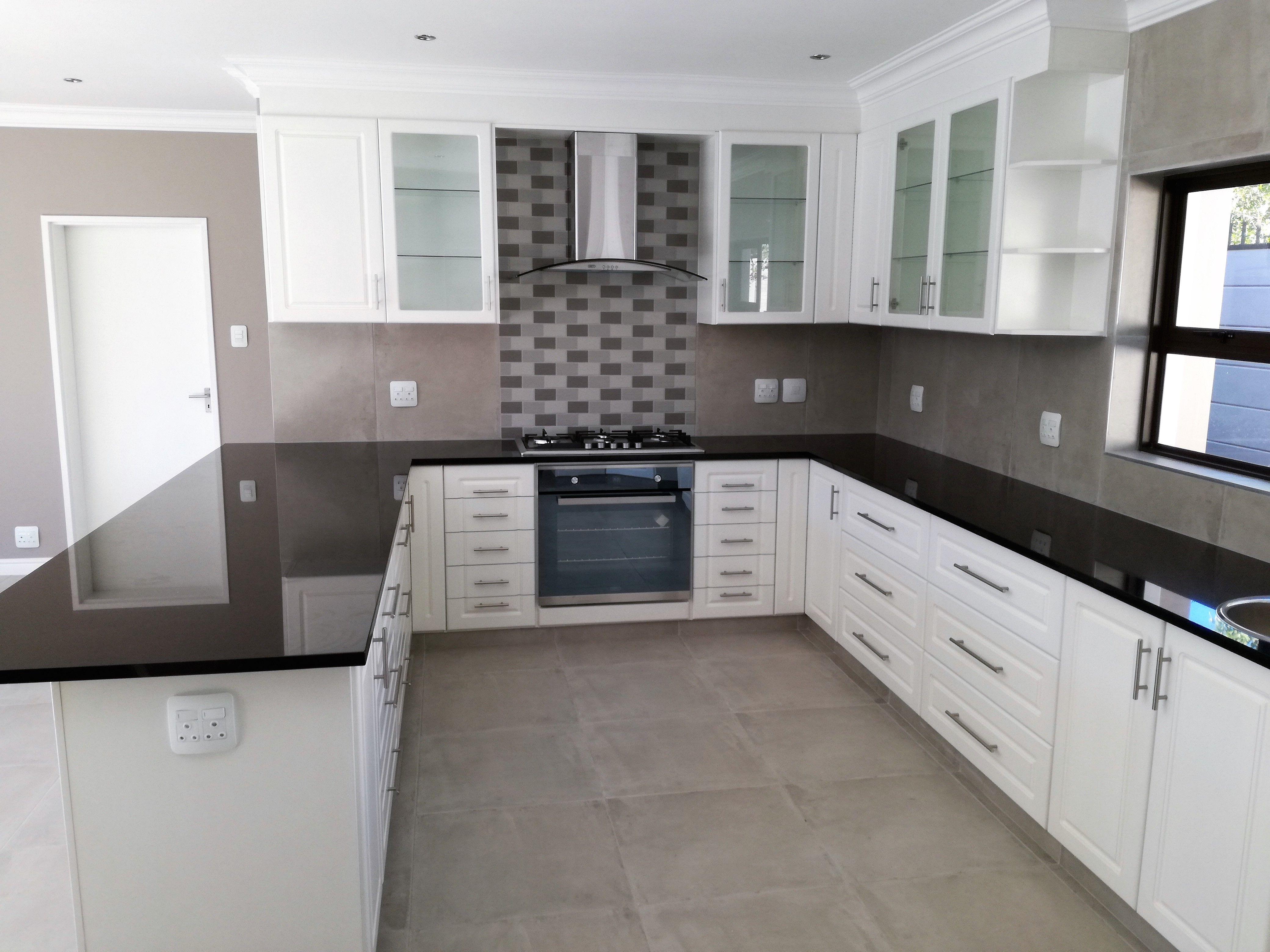 Satin white painted kitchen with Rustenburg granite tops