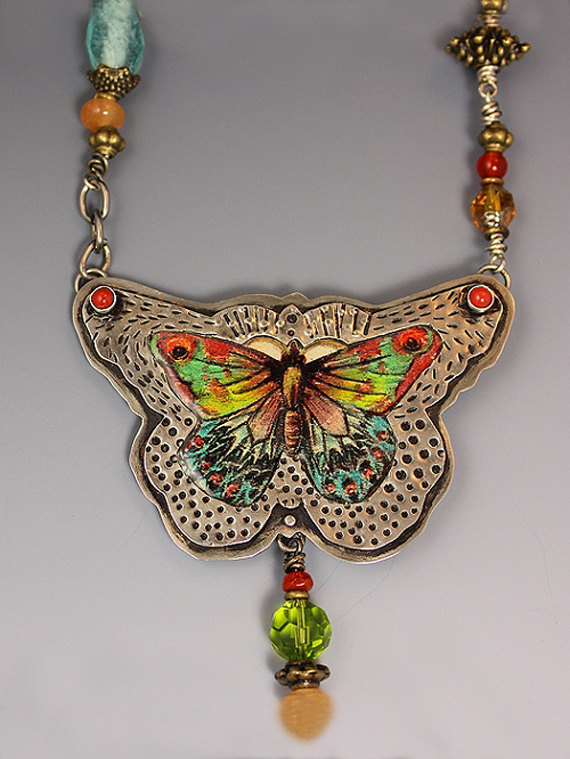 This charming German silver butterfly necklace is hand sawn and detailed with stamped patterns and designs. A lovely hand colored vintage butterfly image is recessed into a cut out indentation and filled with resin. The layers of resin form a slight dome, like looking through old glass windows. 2 Ox-blood coral cabochons set in sterling silver bezels accent the patterned metal frame. Wire wrapped by hand, several semi-precious stones and beads accent the antiqued chain. Gift boxed and…