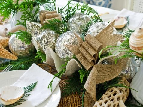 A centerpiece doesn't have to be a fussy (and expensive) floral arrangement. Fill a large shell, basket or silver bowl with mercury glass ornaments, sprigs of fresh greenery and some loosely-looped lengths of burlap ribbon. An arrangement like this is low, so guests can see over it to converse while eating.