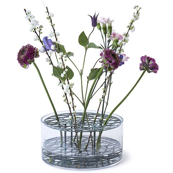 Klong's Äng, designed by Eva Schildt, is an intriguing vase that makes creating flower arrangements easy. The name Äng, Swedish for meadow, refers to the way flowers stand in the vase: the double-tiered brass frame separates the stems and holds them upright.