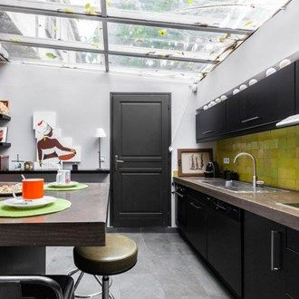 Parisian style kitchen with a glass roof and 'Zellige' lime tiles by Emery & Cie