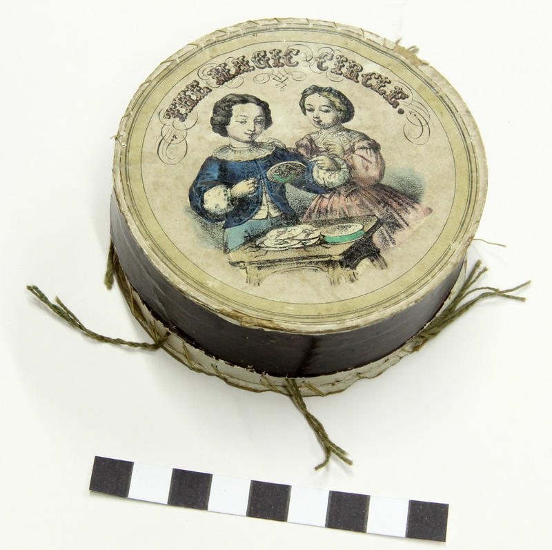 A round cardboard box containing twelve thaumatropes with hand coloured illustrations.  THE MAGIC CIRCLE  is marked on the lid together with an illustration of the thaumatropes being used. 1/6 on base. The thaumatropes are accompanied by two letters written to Mr Warren during 1953 by John Barnes. #magiccircle